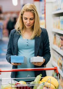 woman comparing food labels in store