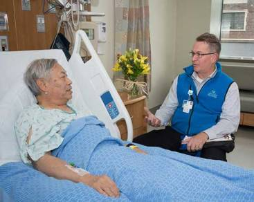 Patient peer partner volunteer speaks with orthopedics patient.